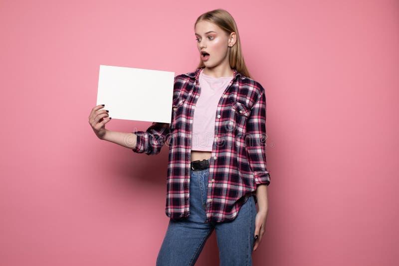 Entsetzte umgekippte junge Frau in der zuf?lligen Kleidung, wei?en leeren freien Raum f?r Ihren Text halten stockbilder