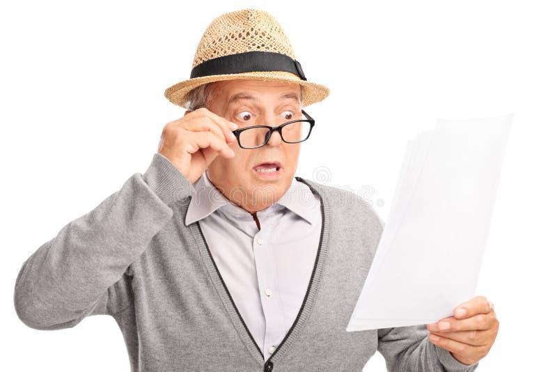 Entsetzter älterer Herr, der die Rechnungen betrachtet stockfotos