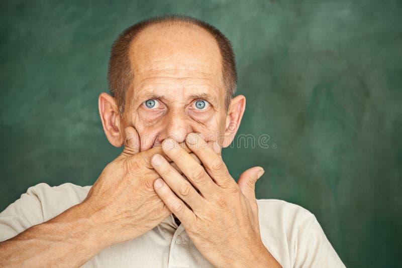 Entsetzter älterer Herr, der seine Hand gegen seinen Mund hält und die Kamera betrachtet stockfoto