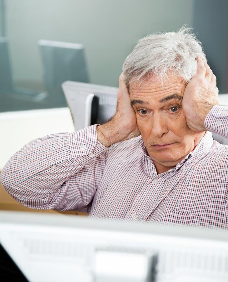 Entsetzter älterer Mann, der Computer im Klassenzimmer betrachtet stockfotos