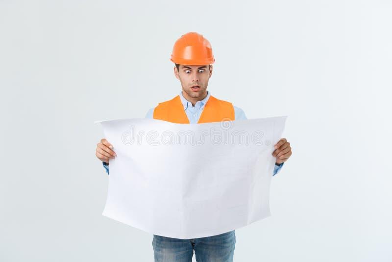 Entsetzter Erbauerbauarbeiter verwahrt in der Hand einen PlanDokumententwurf auf grauem Hintergrund lizenzfreies stockfoto
