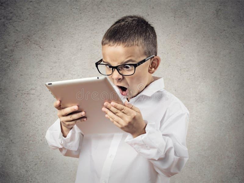 Entsetzter, frustrierter Junge, der Auflagencomputer verwendet stockfotos