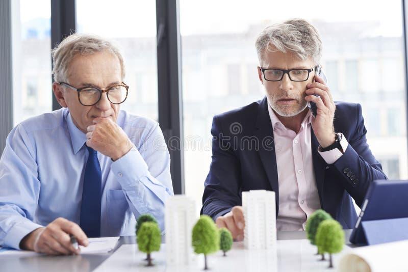 Entsetzter Geschäftsmann, der durch Handy während des Geschäftstreffens spricht stockbilder