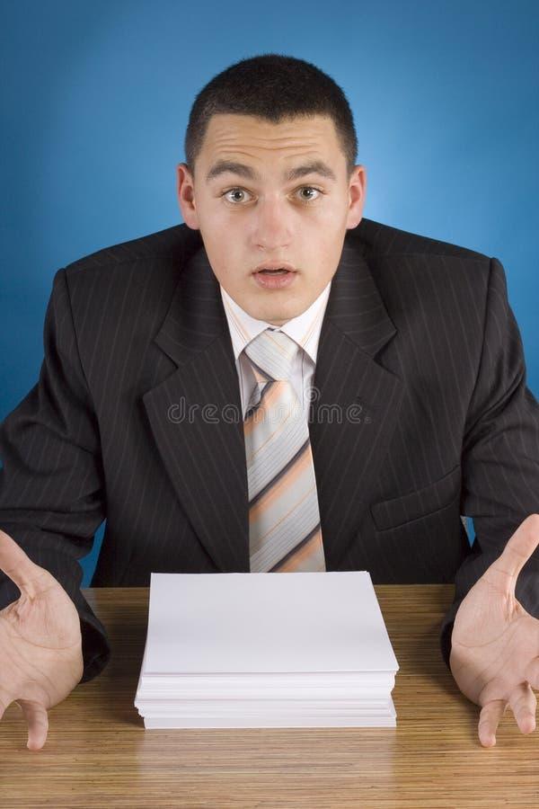 Entsetzter Geschäftsmann am Stapel der Dokumente stockfoto