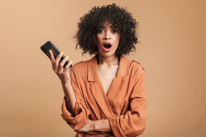 Entsetzter hübscher afrikanischer Frauenholding Smartphone und Betrachten der Kamera lizenzfreies stockbild