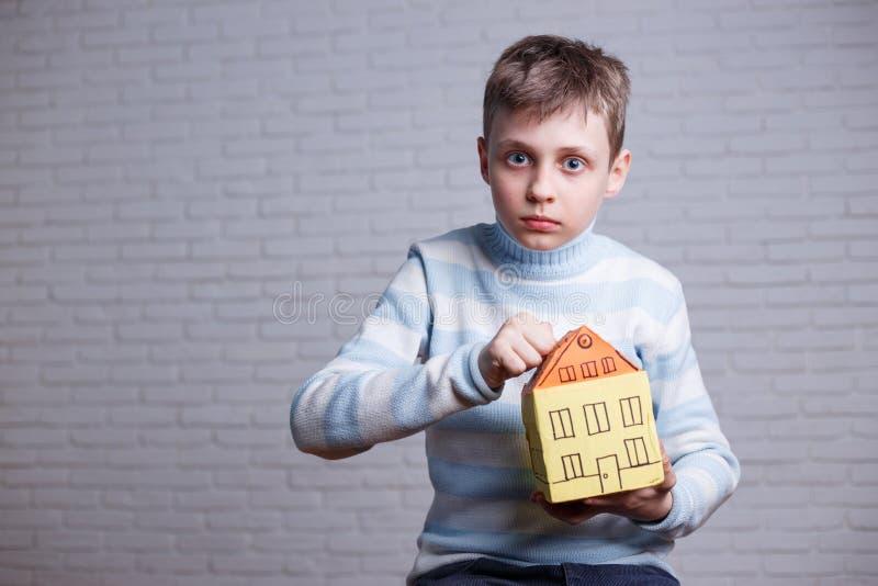 Entsetzter Junge, der zum Pappspielzeughaus klopft Jugendlich und Kinder p stockfotos