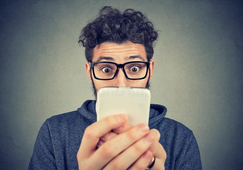 Entsetzter junger Mann, der Smartphone betrachtet stockfotos
