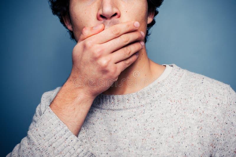 Entsetzter junger Mann mit seiner Hand auf seinem Mund stockbild