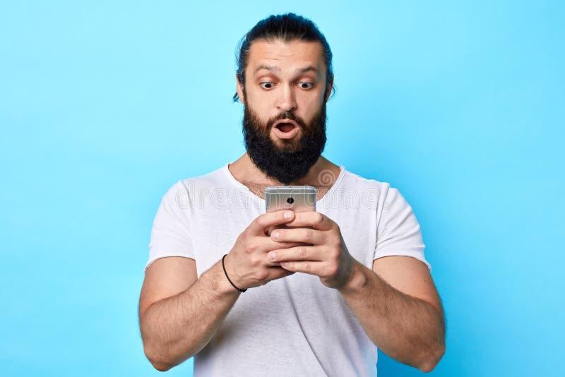 Entsetzter junger starker muskulöser Mann, der Handy betrachtet lizenzfreies stockfoto
