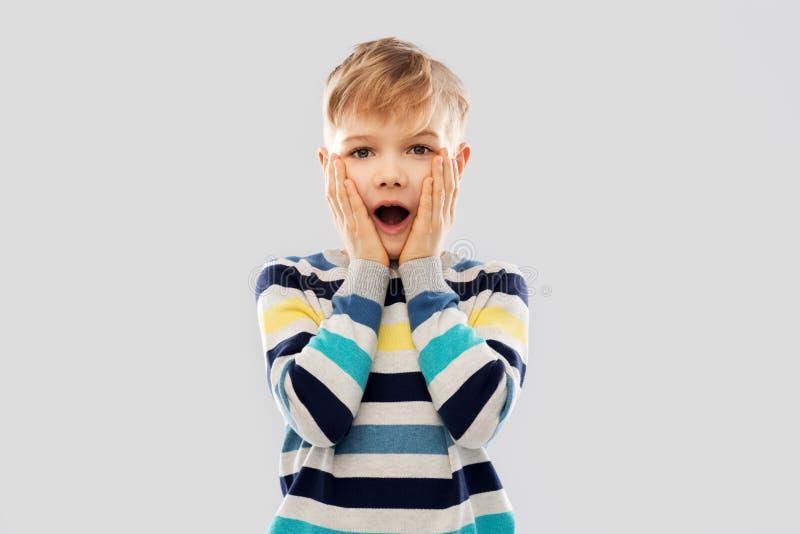 Entsetzter kleiner Junge in gestreiftem Pullover stockfotografie