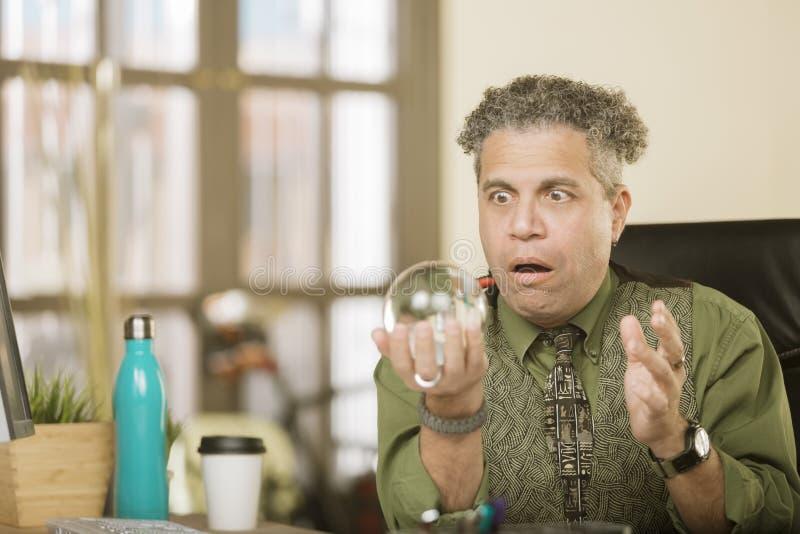 Entsetzter kreativer Mann mit Crystal Ball stockfotos