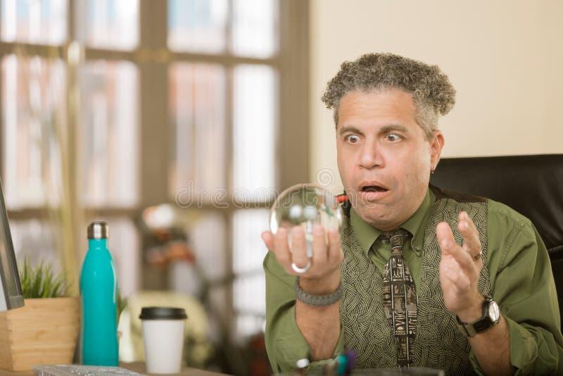 Entsetzter kreativer Mann mit Crystal Ball lizenzfreie stockfotografie