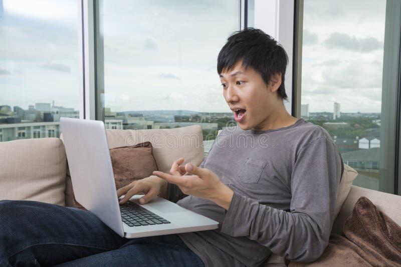 Entsetzter Mann, der zu Hause Laptop auf Sofa verwendet lizenzfreie stockfotos