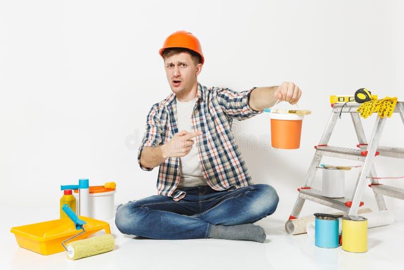 Entsetzter Mann im orange Schutzhelm, der auf Boden mit Farbendose, Instrumente für die Erneuerungswohnung lokalisiert sitzt lizenzfreies stockbild