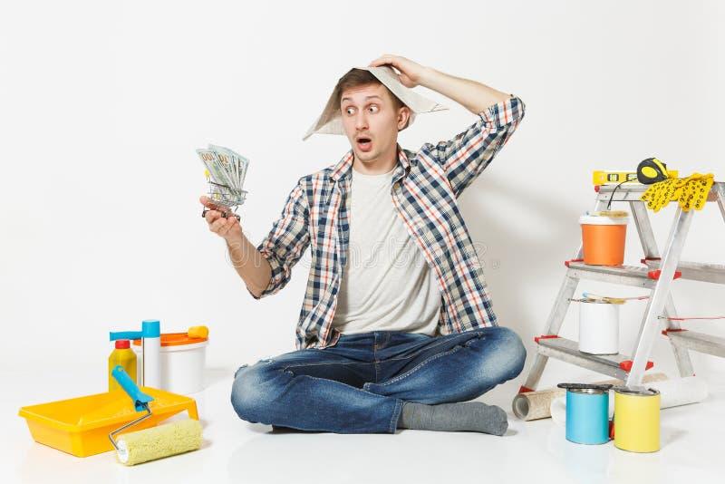 Entsetzter Mann im Zeitungshut hält Bündel Dollar, Bargeld Instrumente für die Erneuerungswohnung lokalisiert auf Weiß lizenzfreies stockbild