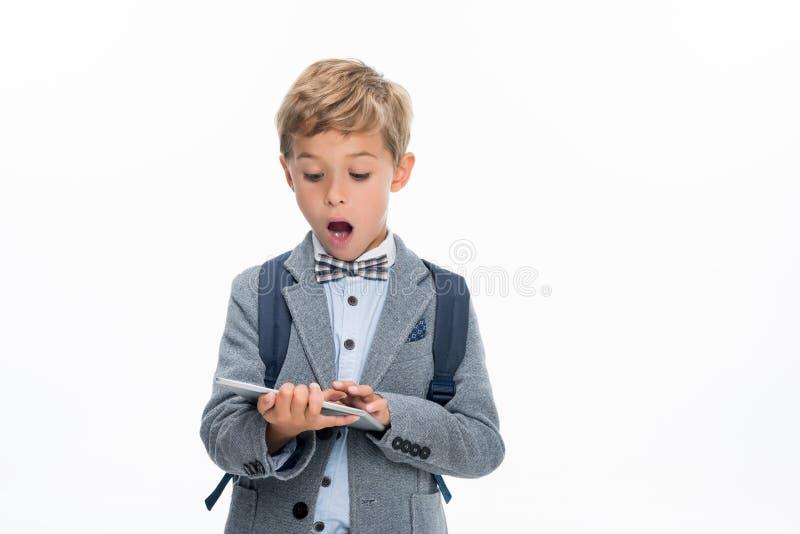 Entsetzter Schüler, der Tablette verwendet stockfotografie