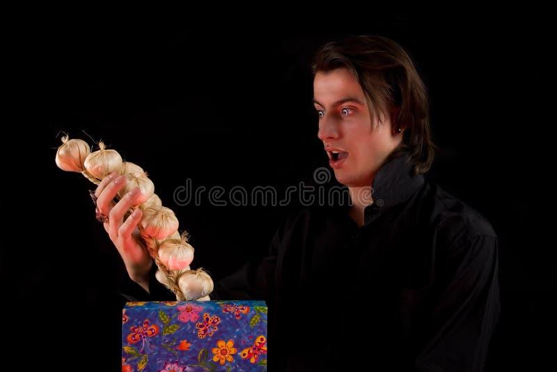 Entsetzter Vampir mit dem Geschenkkasten, der Knoblauch herausnimmt stockfotos