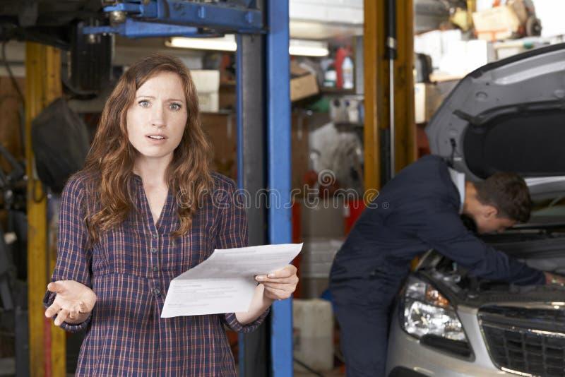 Entsetzter weiblicher Kunde, der Garage Bill betrachtet lizenzfreies stockbild