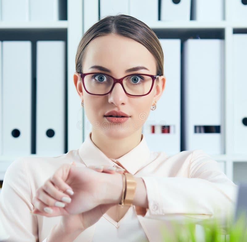 Entsetzter weiblicher Manager, der die Kamera zeigt auf ihre Armbanduhr nahe einem Stapel von Dokumenten betrachtet Kalender mit  stockbilder