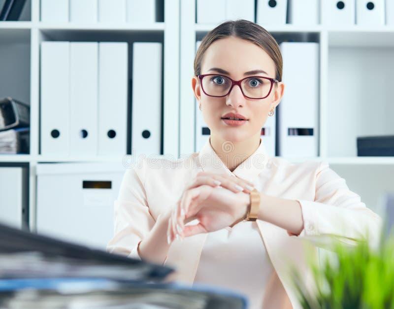 Entsetzter weiblicher Manager, der die Kamera zeigt auf ihre Armbanduhr nahe einem Stapel von Dokumenten betrachtet Kalender mit  lizenzfreie stockfotografie