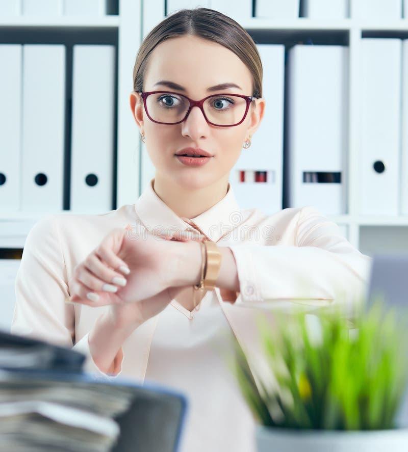 Entsetzter weiblicher Manager, der ihre Uhr nahe einem Stapel von Dokumenten betrachtet Kalender mit Datums-Ikone innerhalb des Z lizenzfreies stockbild