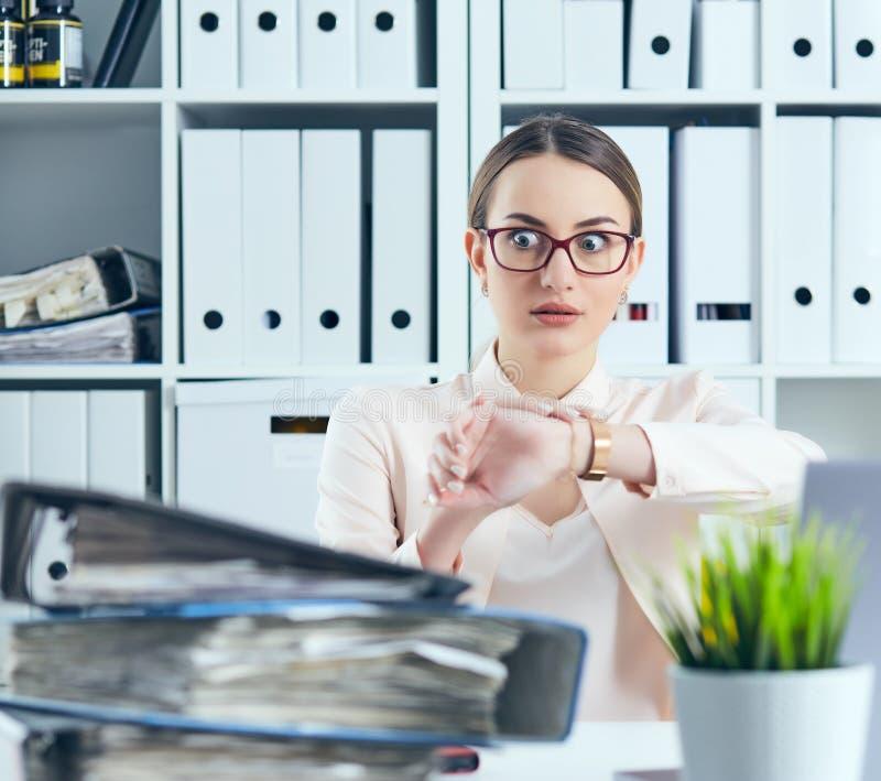 Entsetzter weiblicher Manager, der ihre Uhr nahe einem Stapel von Dokumenten betrachtet Kalender mit Datums-Ikone innerhalb des Z stockfoto