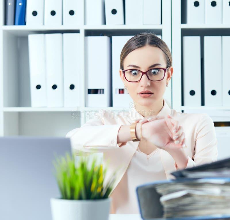 Entsetzter weiblicher Manager, der ihre Uhr nahe einem Stapel von Dokumenten betrachtet Kalender mit Datums-Ikone innerhalb des Z stockbild