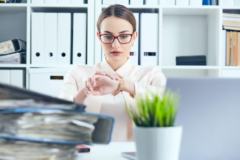 Entsetzter weiblicher Manager, der ihre Uhr nahe einem Stapel von Dokumenten betrachtet Kalender mit Datums-Ikone innerhalb des Z lizenzfreie stockfotos