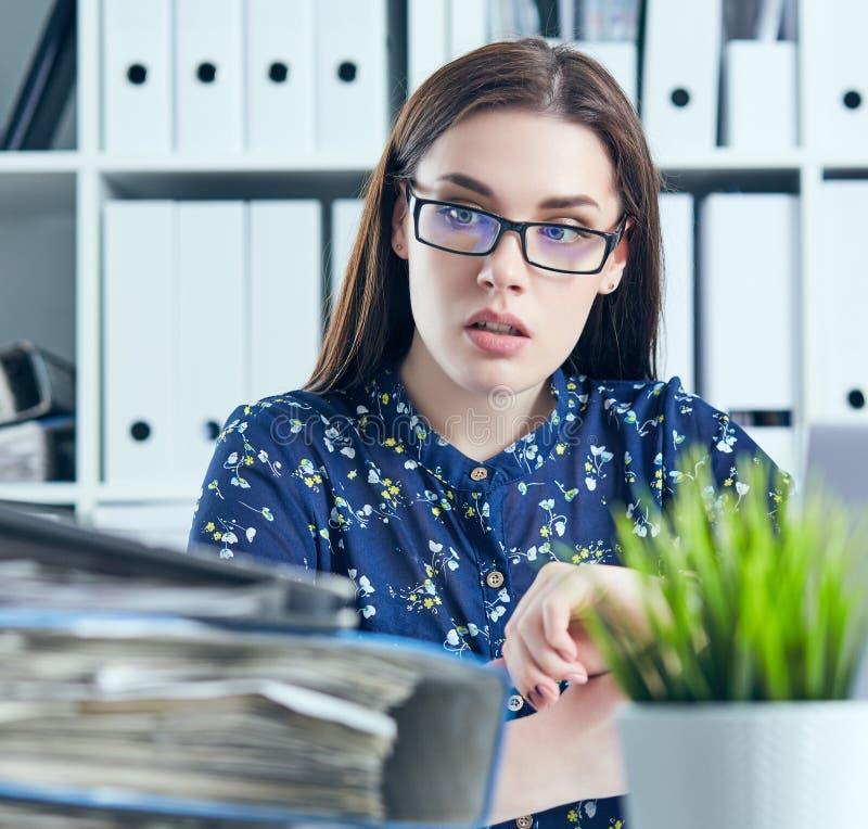 Entsetzter weiblicher Manager, der ihre Uhr und dem Stapel von Dokumenten betrachtet Kalender mit Datums-Ikone innerhalb des Ziel stockfoto