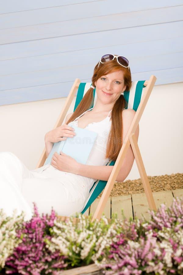 Entspannen sich rote Haarfrau der Sommerterrasse im deckchair stockfotos