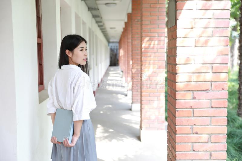 Entspannen Sie sich asiatischen chinesischen hübschen Mädchenabnutzungsstudenten, den Anzug in der Schule Freizeit gelesenes Buch stockfotos