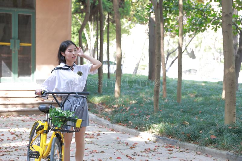 Entspannen Sie sich asiatischen chinesischen hübschen Mädchenabnutzungsstudenten, den Anzug in der Schule Freizeitfahrfahrrad im  lizenzfreies stockbild