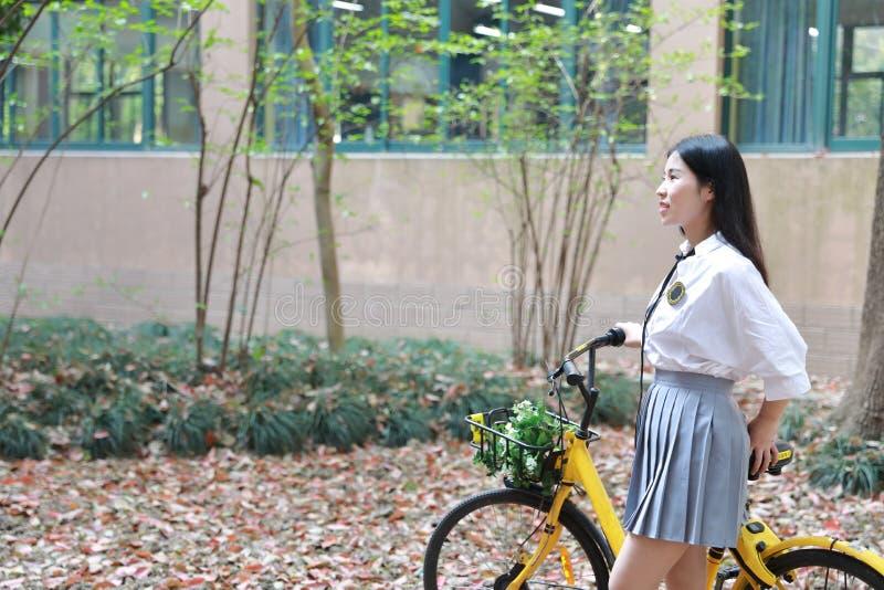 Entspannen Sie sich asiatischen chinesischen hübschen Mädchenabnutzungsstudenten, den Anzug in der Schule Freizeitfahrfahrrad im  lizenzfreie stockbilder