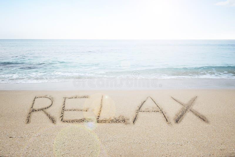 Entspannen Sie sich das Wort, das im Sand auf sonnigem Strand handgeschrieben ist stockfotos