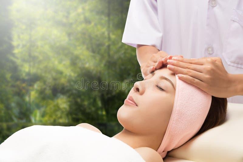Entspannen Sie sich empfangende Gesichtsmassage der schönen asiatischen Frau lizenzfreie stockfotografie
