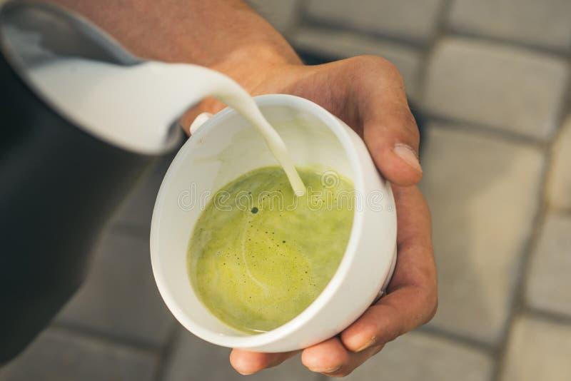 Entspannen Sie sich im Café oder Kaffeestube und Trinken matcha Latteteezeremonie, gießen Milch perfekter Morgen mit Rohkaffee lizenzfreie stockfotografie