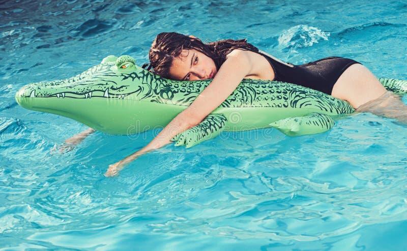 Entspannen Sie sich im Luxusswimmingpool Modekrokodilleder und -m?dchen im Wasser Sommerferien und -reise zum Ozean stockfoto