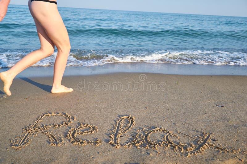 Entspannen Sie sich Mitteilung auf dem Strandsand und Frau lief - Ferien und Reise concep stockbild