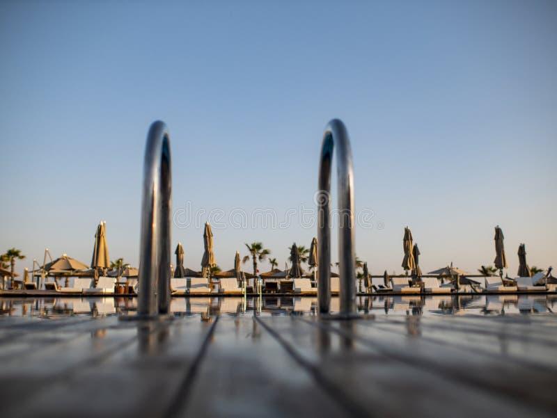 Entspannen Sie sich nahe Pool mit dem Handlauf, sunbeds, Sonnenruhesesseln und Sonnenschirmen, die auf Touristen im tropischen Er lizenzfreie stockbilder