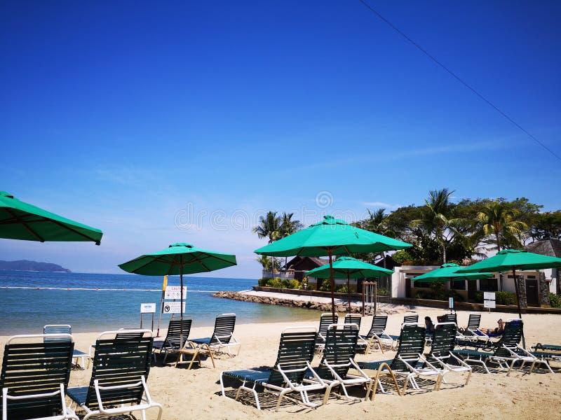 Entspannen Sie sich und genießen Sie auf dem Strand mit faulen Stühlen auf Strand und schönem blauem Himmel oben lizenzfreie stockbilder