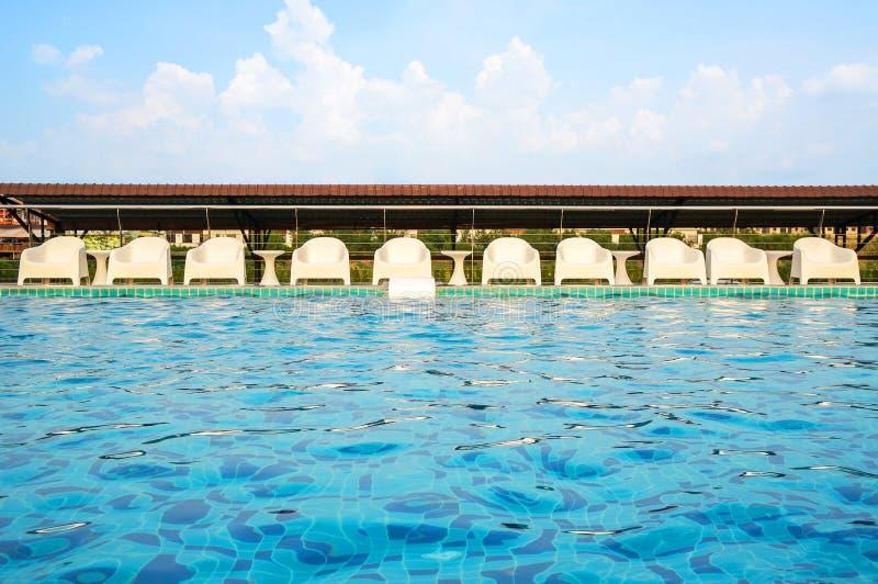 Entspannen Sie sich weiße Stühle, indem Sie Poolside schwimmen lizenzfreie stockfotos