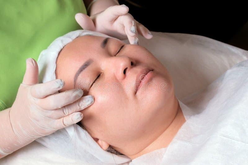 Entspannend und weibliches cosmetological Verfahren verjüngend Die Hände eines Kosmetikers in den weißen Handschuhen die Creme um lizenzfreies stockfoto