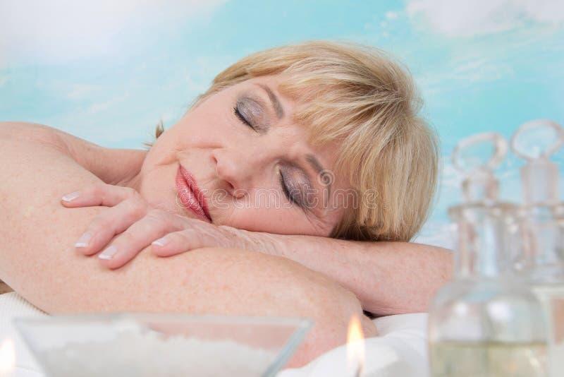 Entspannende ältere Frau im Badekurort lizenzfreies stockfoto