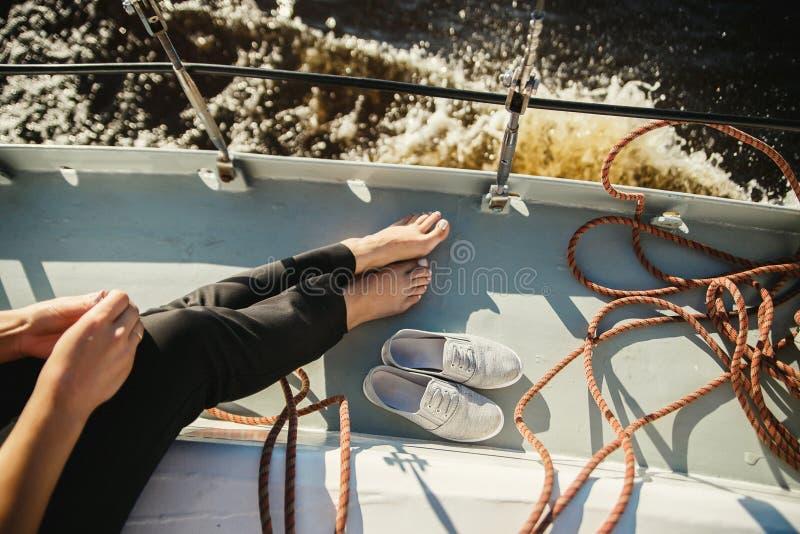 Entspannende Frau auf der Yacht im Meer oder im Fluss Draufsichtbeine und weiße Schuhe auf Plattform lizenzfreie stockbilder