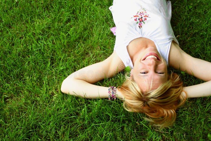 Entspannende Frau, die auf Gras legt lizenzfreie stockfotografie