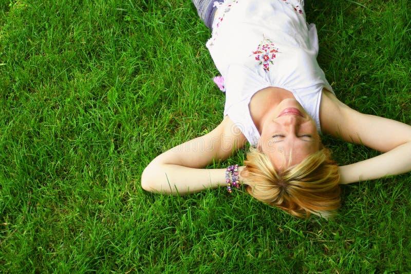 Entspannende Frau, die auf Gras legt stockfoto