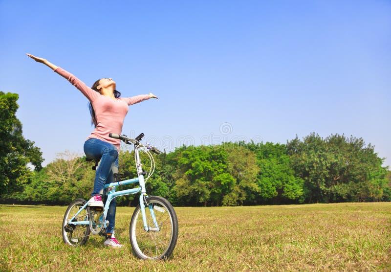 Entspannende Haltung der jungen Frau und Sitzen auf Fahrrad stockfotos