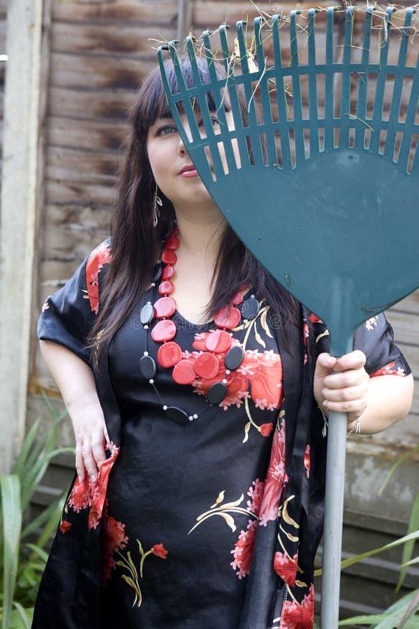 Entspannende Holding des attraktiven Gärtners eine Rührstange stockfoto