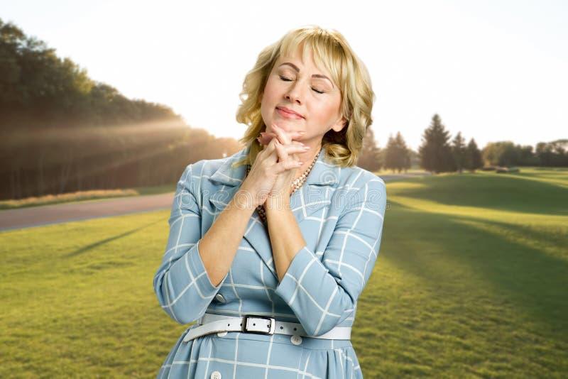 Entspannende reife Frau im Freien lizenzfreie stockbilder