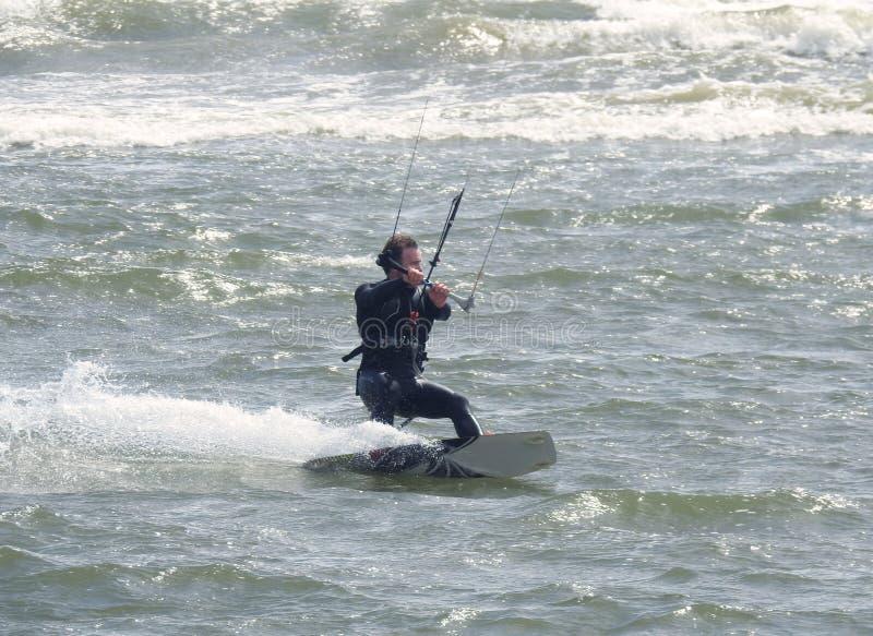 Entspannende Wasser-Sport-Aktion Ein Kiteboarder, welches die Wellen reitet Dorset, Großbritannien Mai 2018 stockbilder